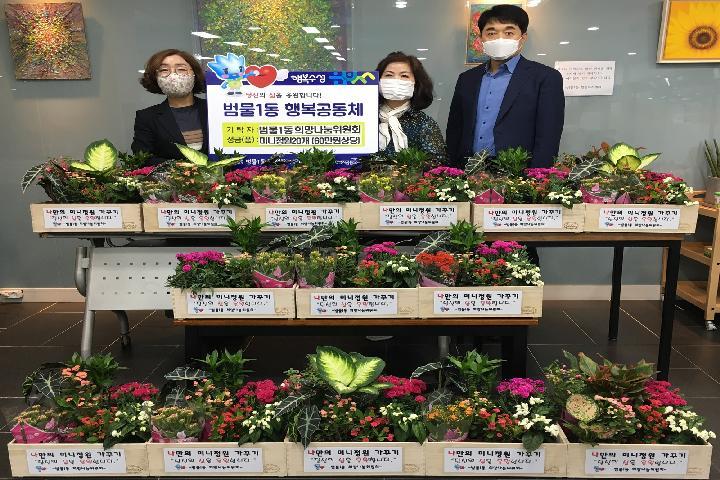 범물1동 희망나눔위원회가 고독사 예방을 위한 '나만의 미니정원'을 전달하고 기념촬영하고 있다.